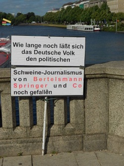 protest sign = how long will the German people put up with the pork-journalism of Bertelsmann, Springer and Co
